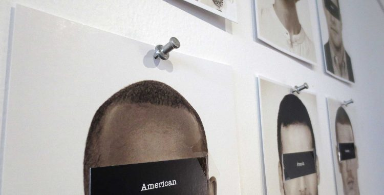 black and white portraits pinned to the wall, with their eyes covered by pieces of black card with national labels